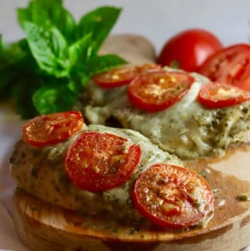 Two baked pesto chicken breasts topped with tomato slices.