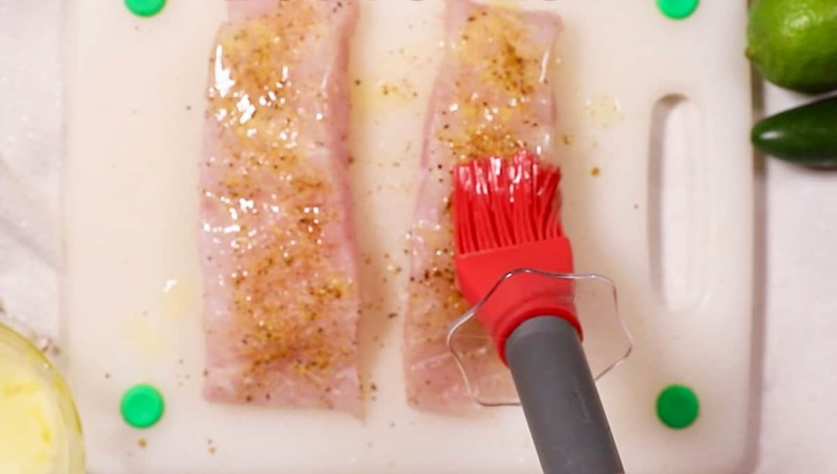 Brushing butter on a fish fillet.