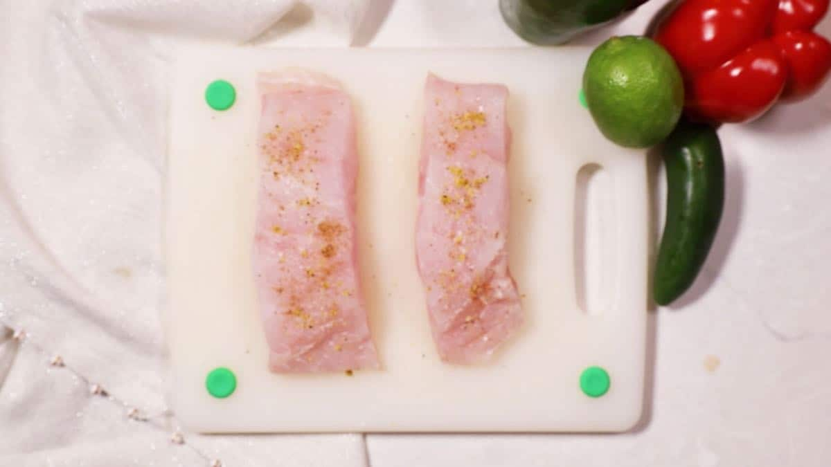 Two grouper fillets on a cutting board.