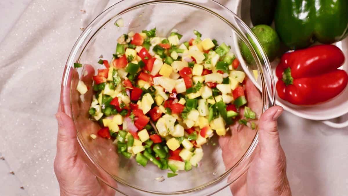 Mango salsa in a clear glass bowl.