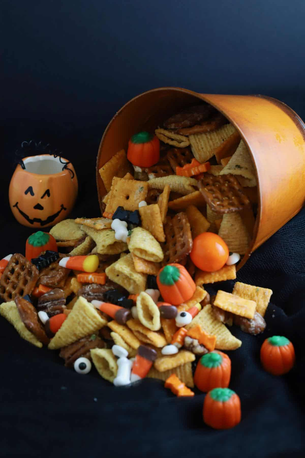 A orange Halloween pail with snack mix falling out of it.