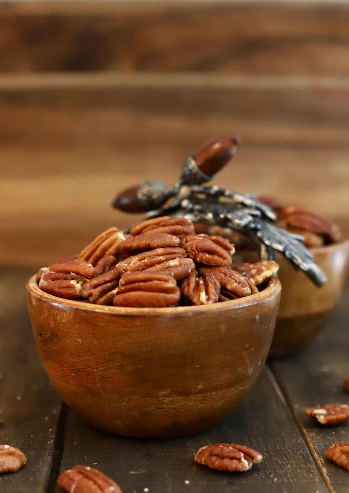 Roasted pecans in a wooden dish.