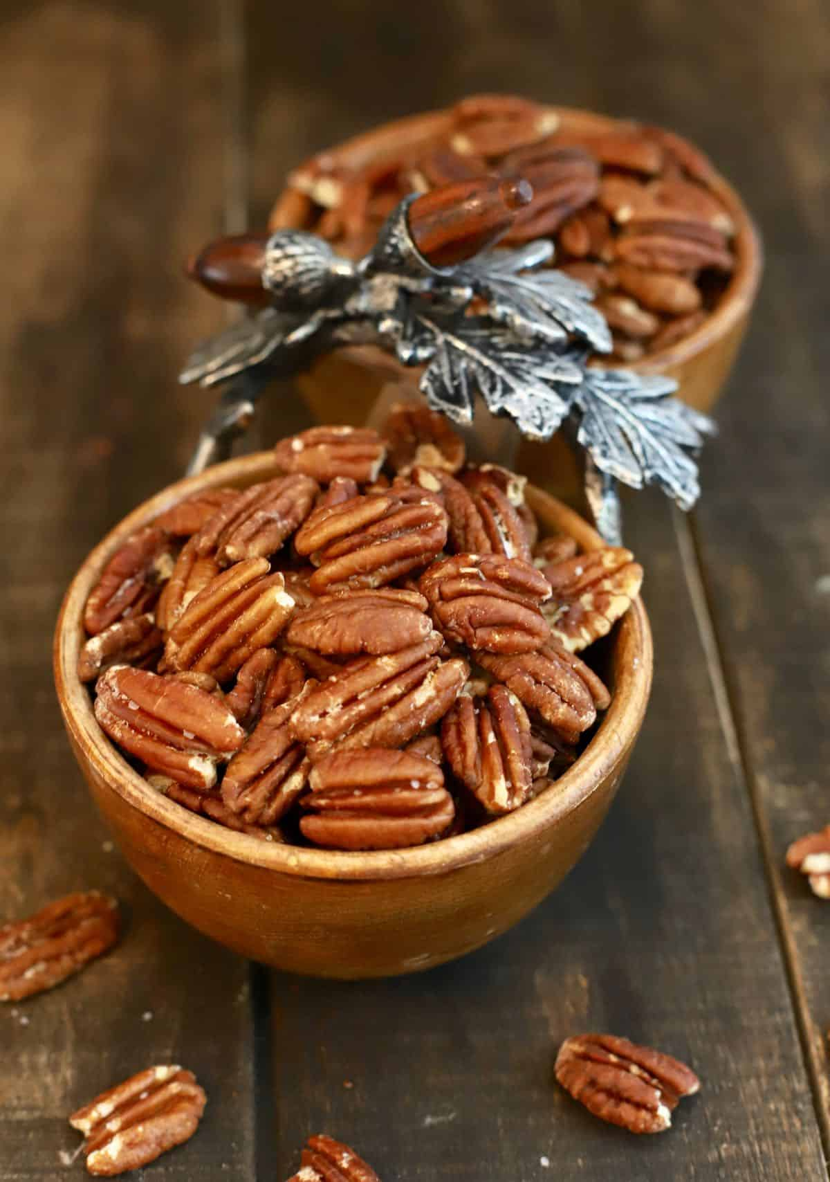 A wooden dish with roasted pecans.