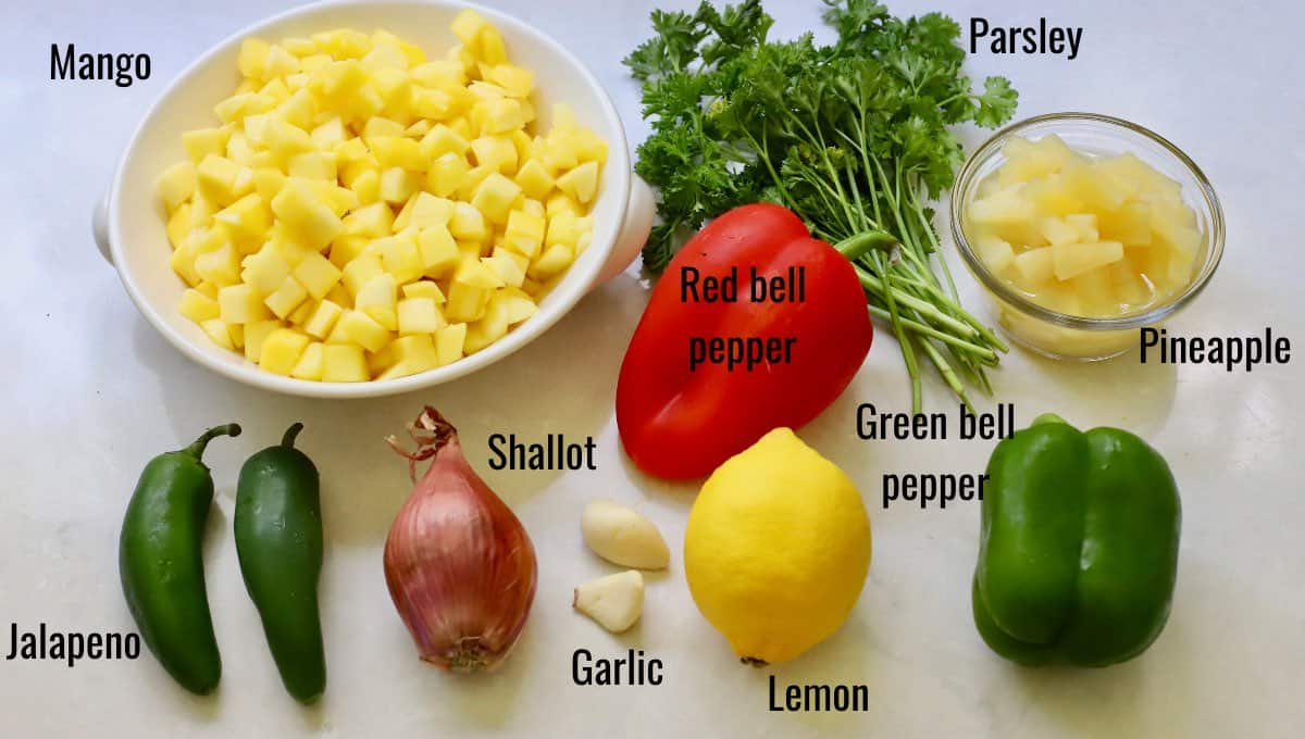 Mango salsa ingredients including mango, bell peppers and pineapple.