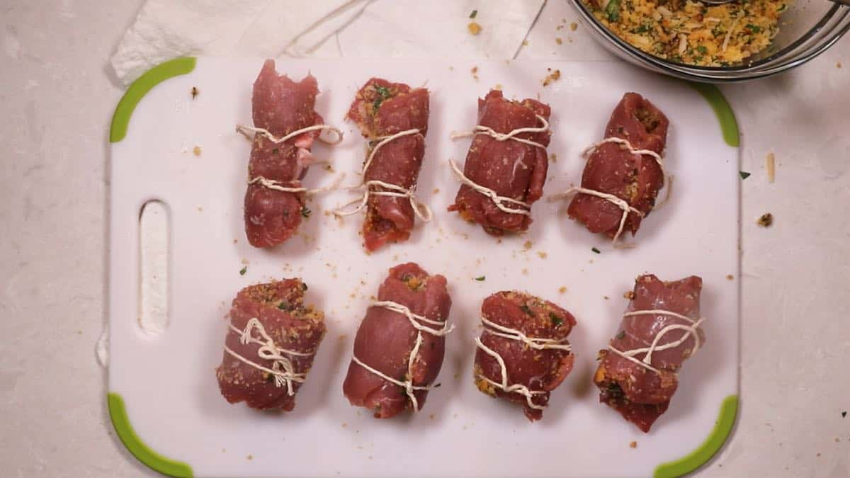 Stuffed pork braciole rolls tied with kitchen string.
