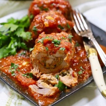 Braciole pork sliced on a plate with marinara sauce.