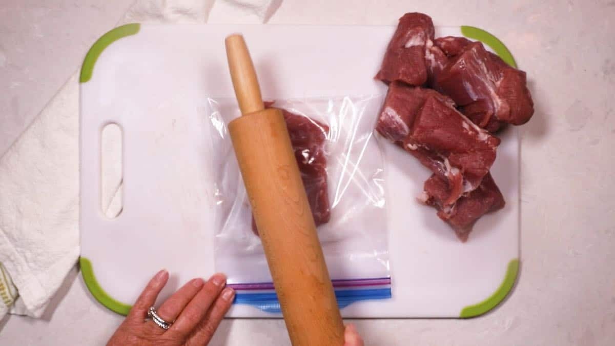 Using a rolling pin to pound a piece of meat thinner.