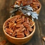 Toasted pecans in a wooden dish with pewter leaves.