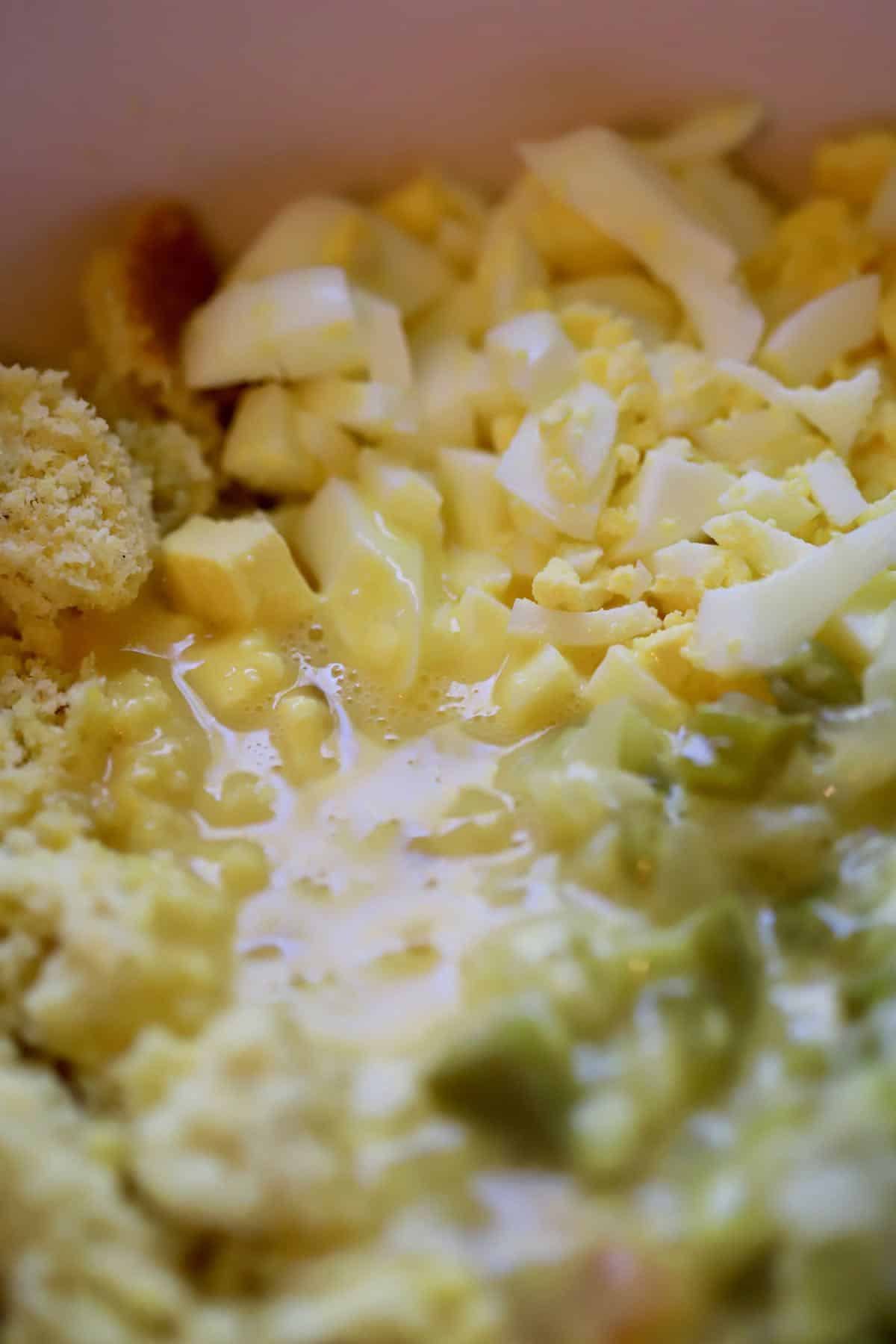 Chopped hard boiled eggs, celery and cornbread in a bowl.