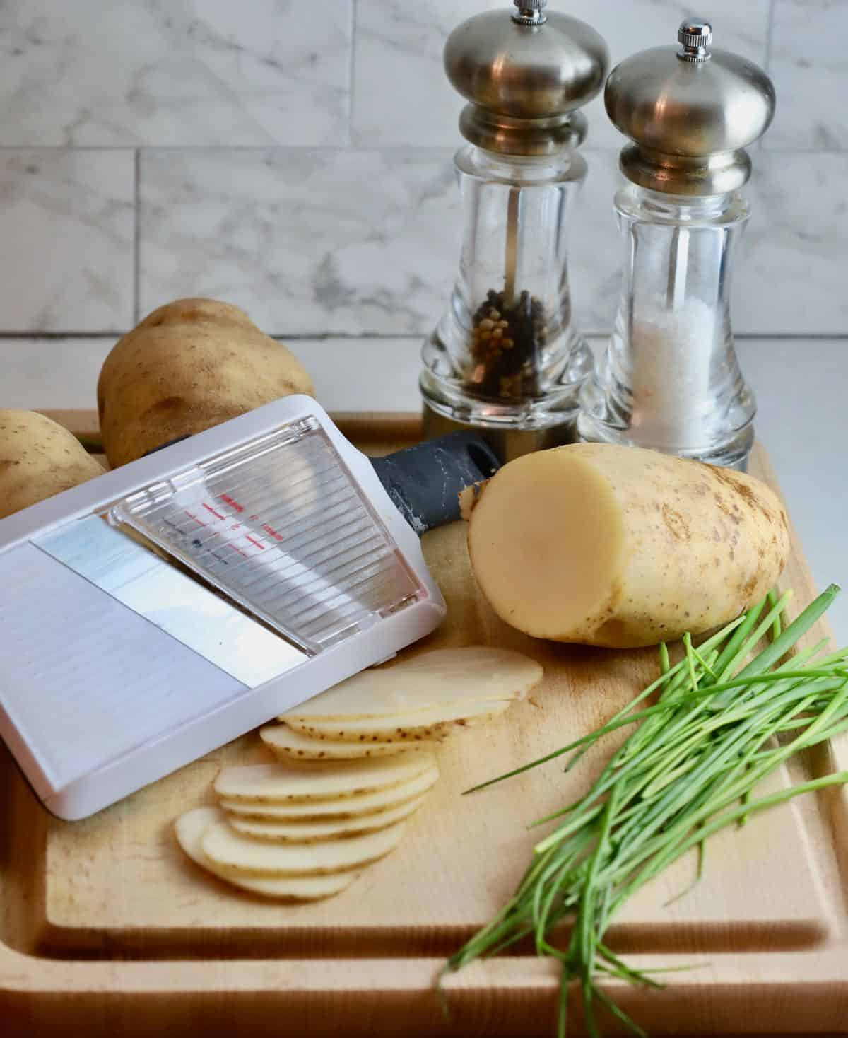 A mandoline with sliced potatoes on a cutting board.