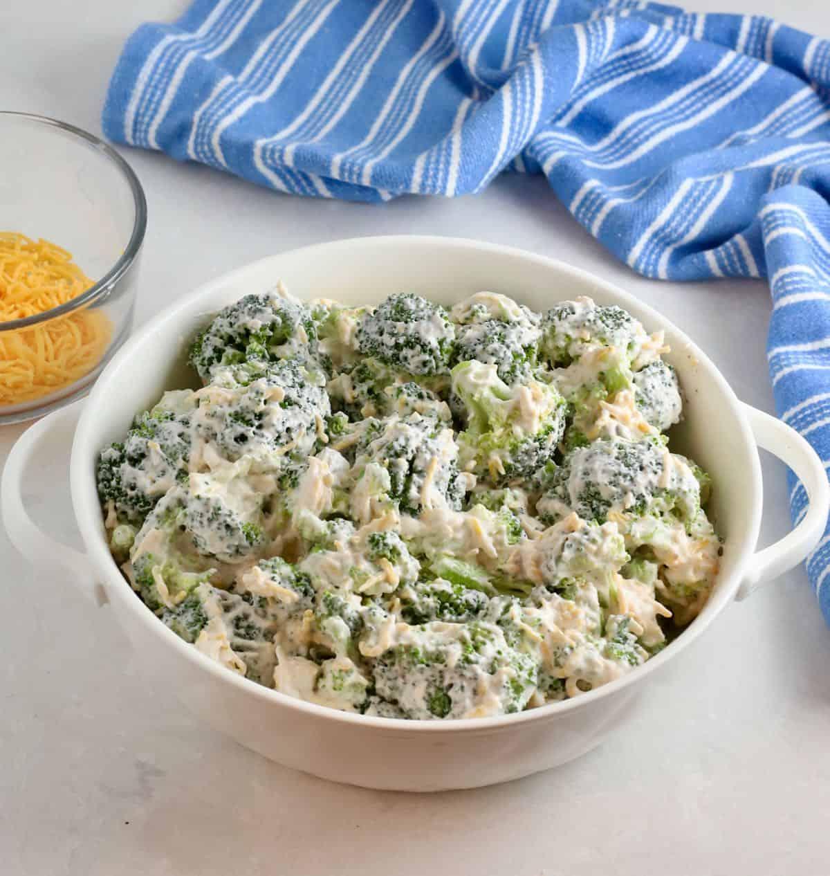 A white baking dish full of broccoli casserole.