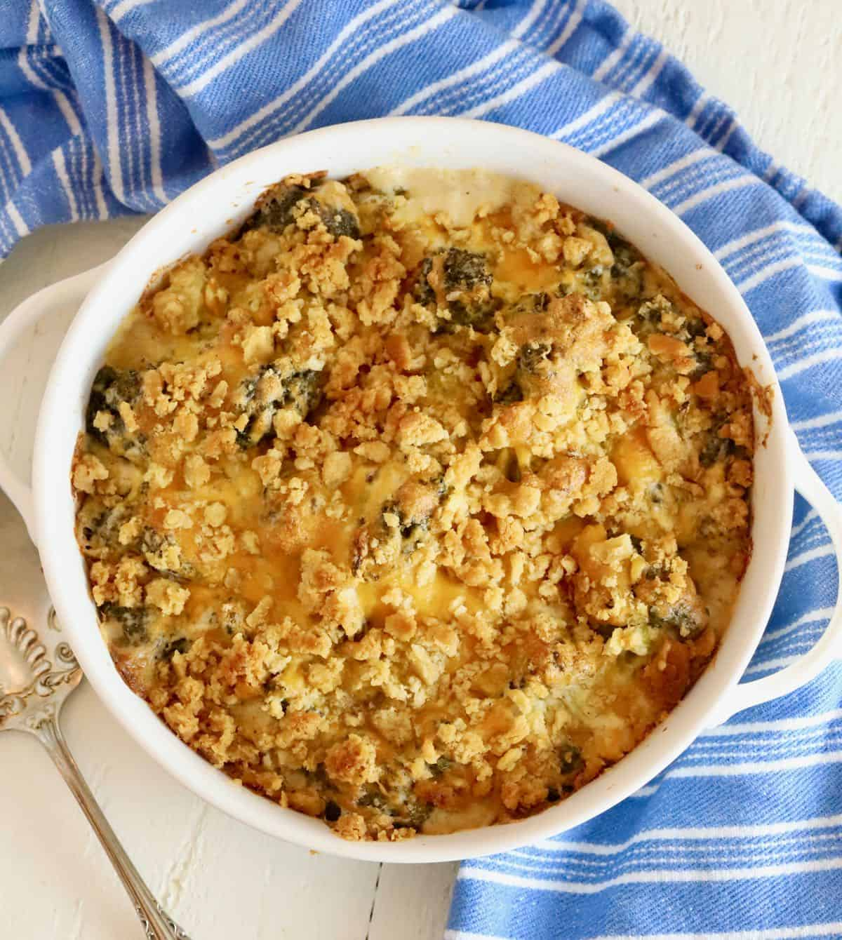 A round white baking dish full of broccoli cheese casserole.
