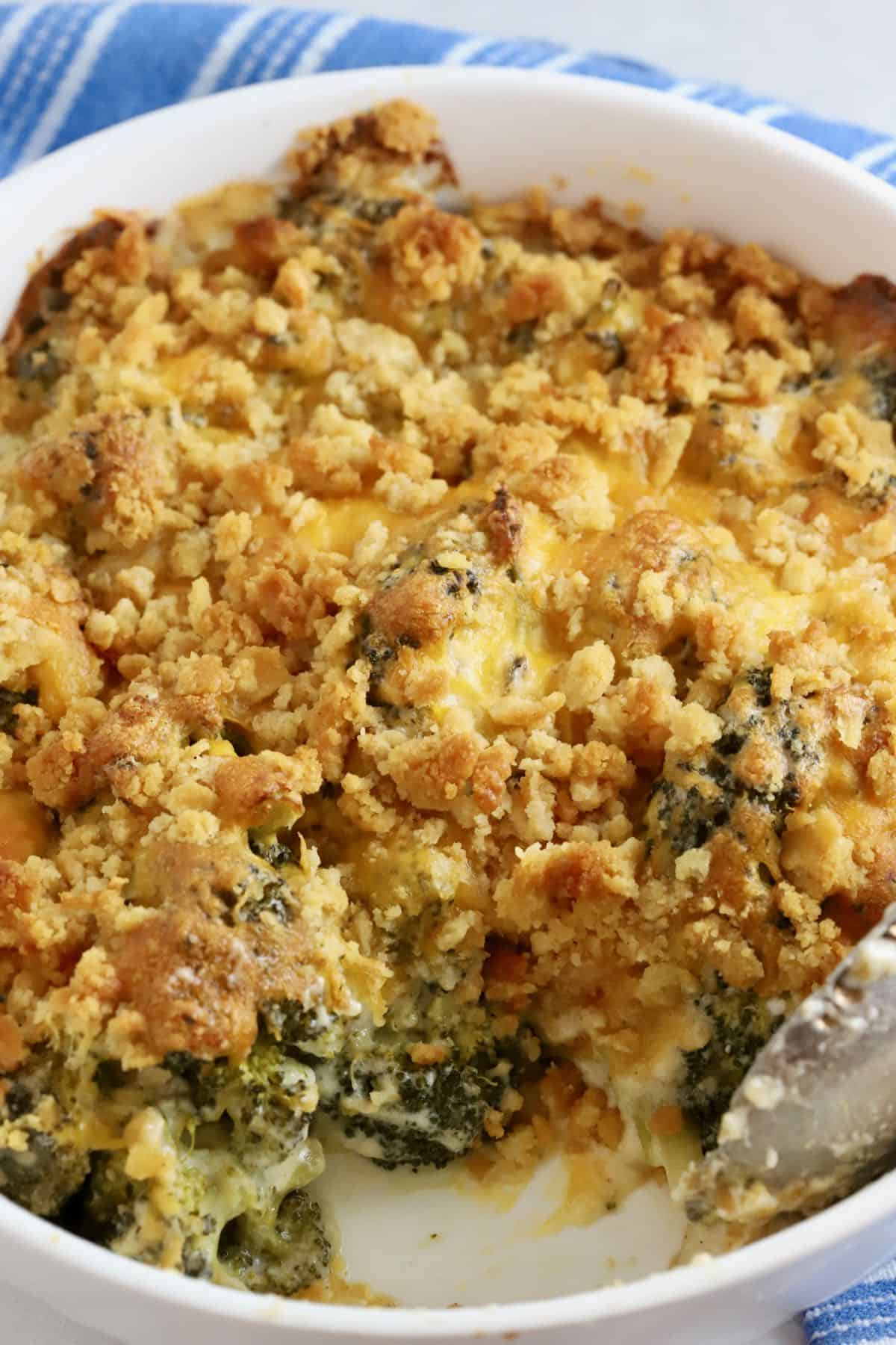 A white baking dish with broccoli casserole with a scoop taken out.