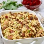 Cornbread dressing with sausage and pecans in a white serving dish.