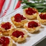 Cranberry brie bites on a white plate with festive napkin.