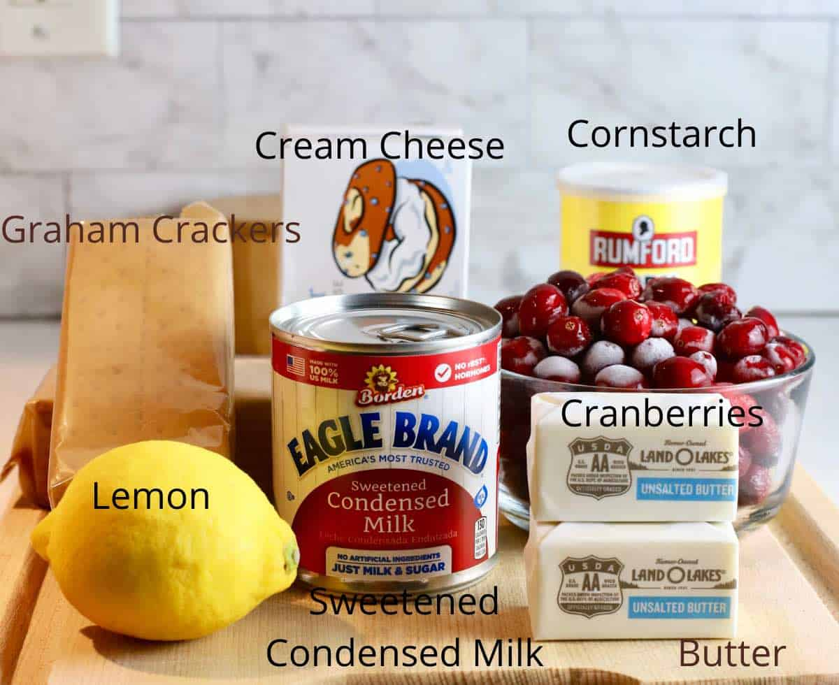 a bowl of cranberries, a lemon and other ingredients to make a cranberry cheesecake.
