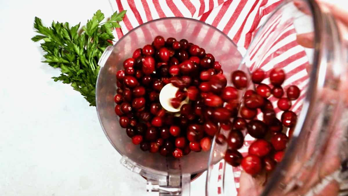 Pouring cranberries into a food processor.
