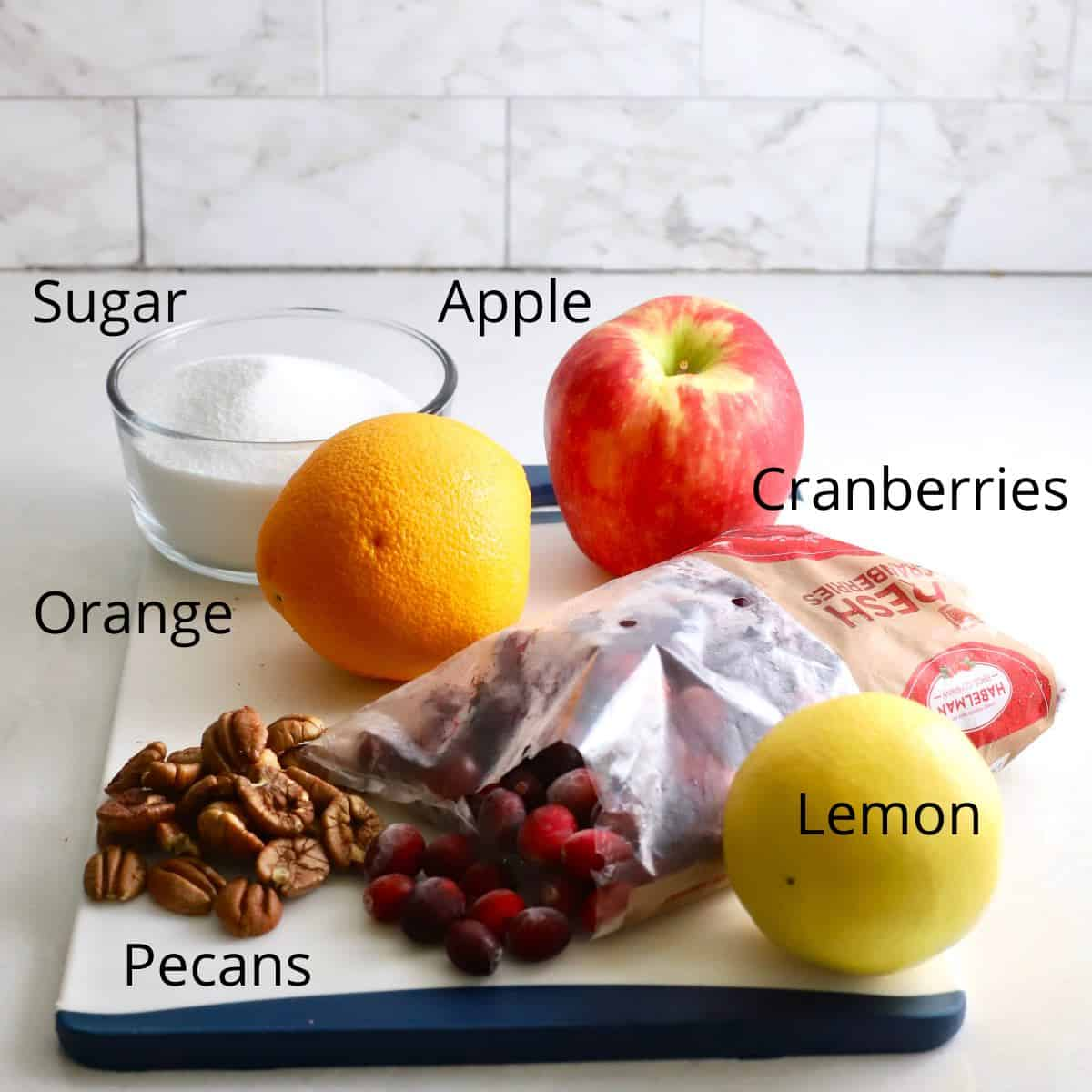 A bag of cranberries, an orange, apple, pecans, and lemon on a cutting board.