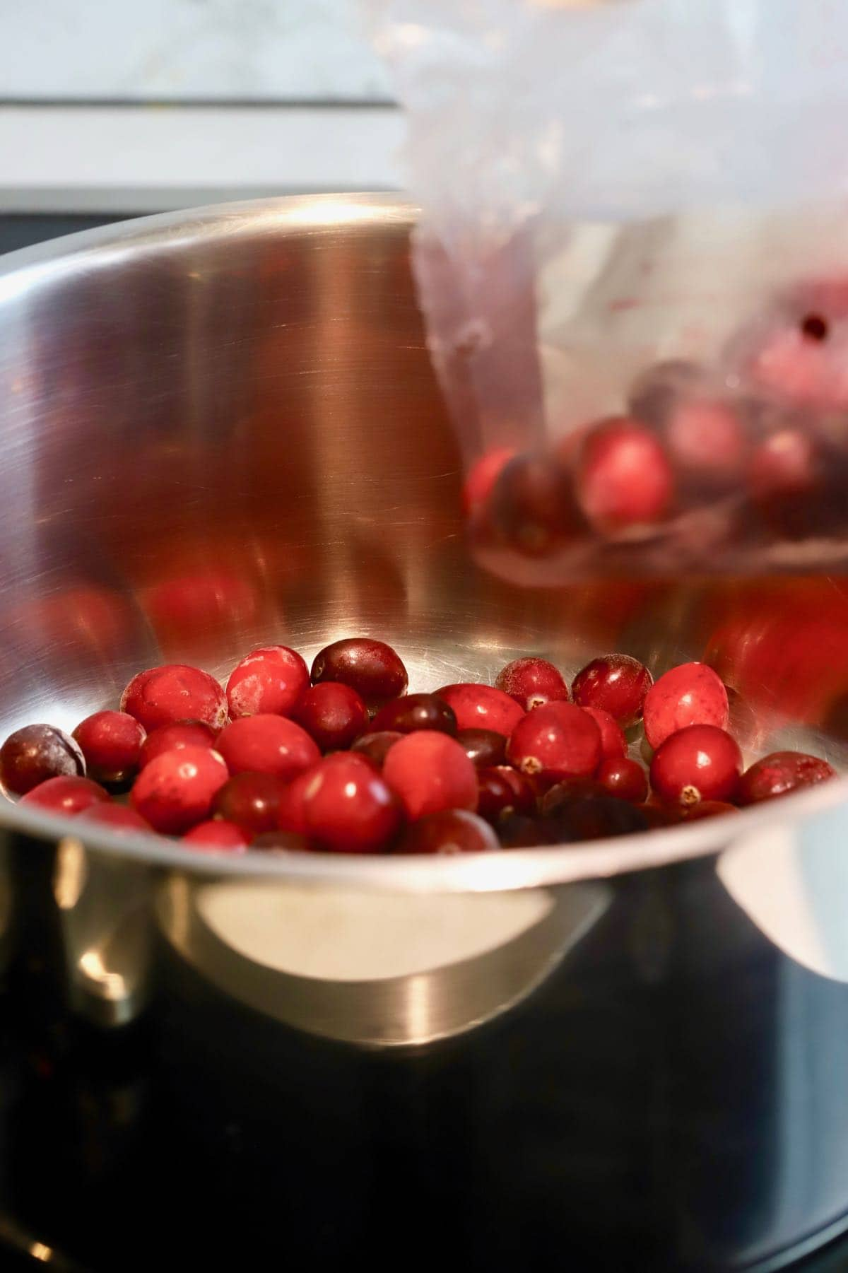 Pouring cranberries into a saucepan.