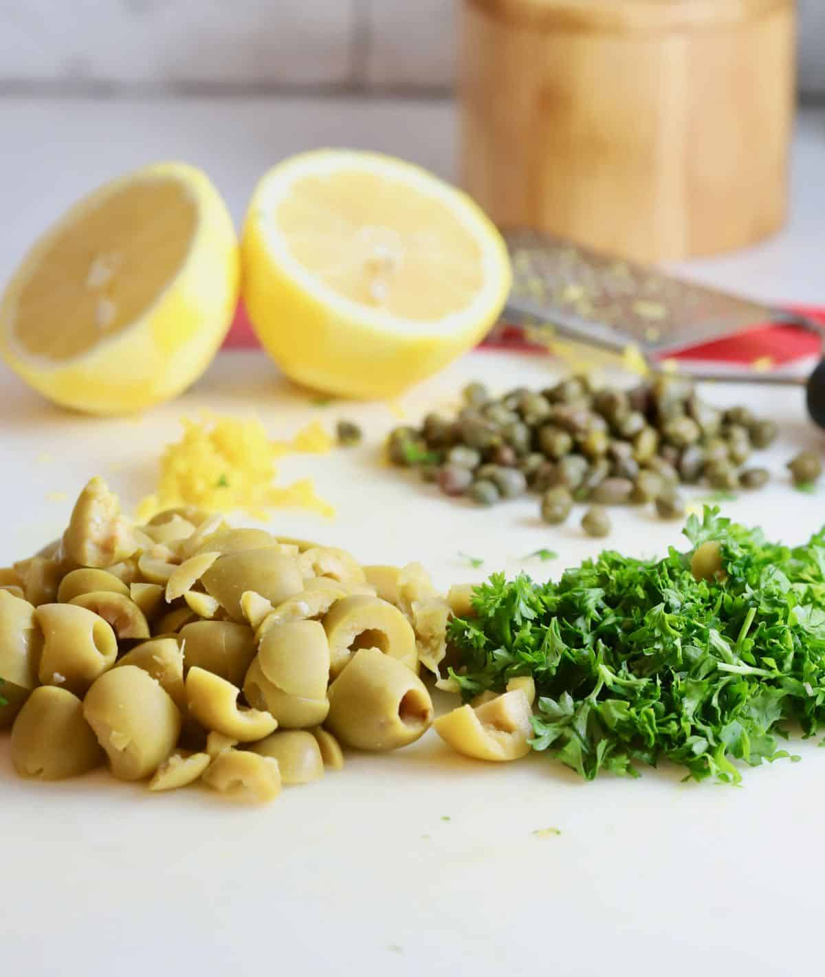 Chopped green olives, capers and slices of lemon.