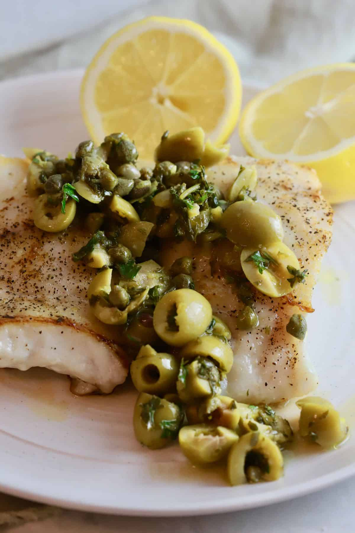Grouper fillets topped with a Mediterranean topping of olives and capers.