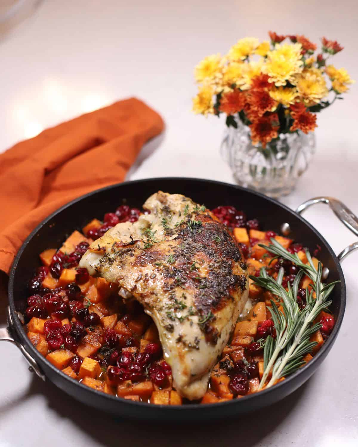 A black skillet with roasted turkey breast, sweet potatoes and cranberries.