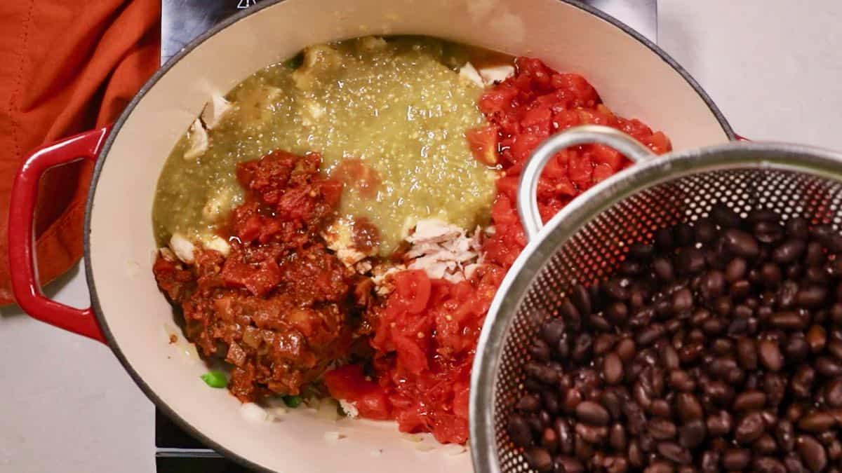 Adding black beans and tomatoes to a Dutch oven.