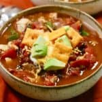 A bowl of turkey chili topped with avocado, cheese and sour cream.