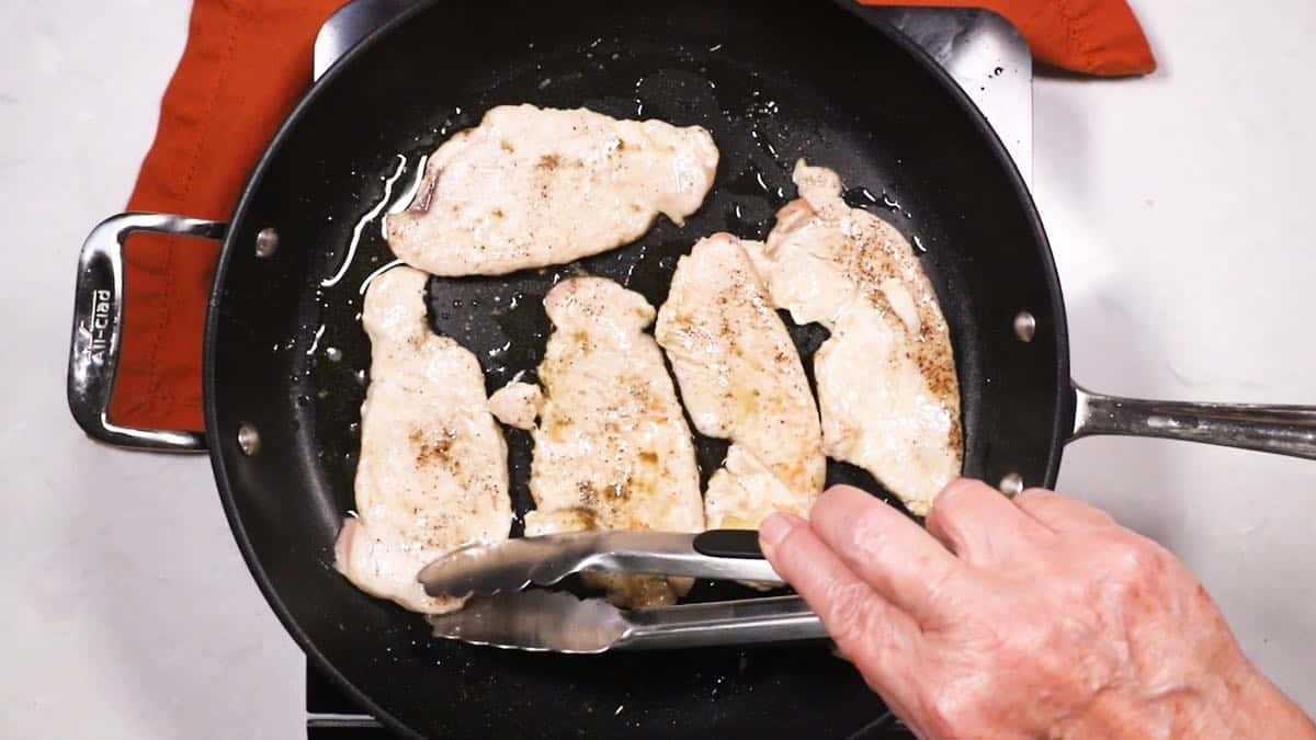 Cooking turkey cutlets in a skillet.