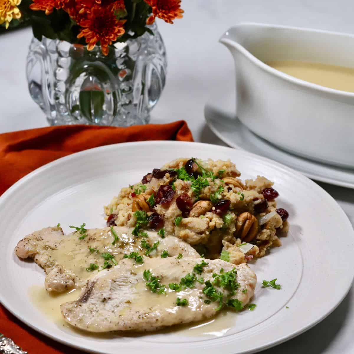 Turkey cutlets topped with gravy and a serving of cornbread dressing on a plate.