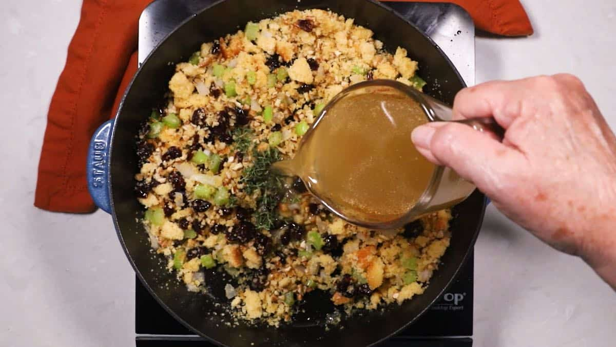 Adding chicken stock to cornbread dressing in a skillet.