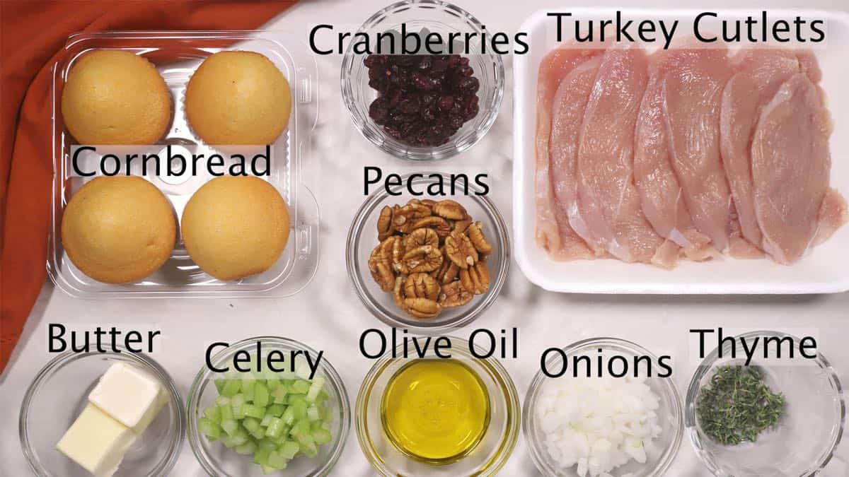 Turkey cutlets, pecans, cranberries, celery, and onion on a cutting board.