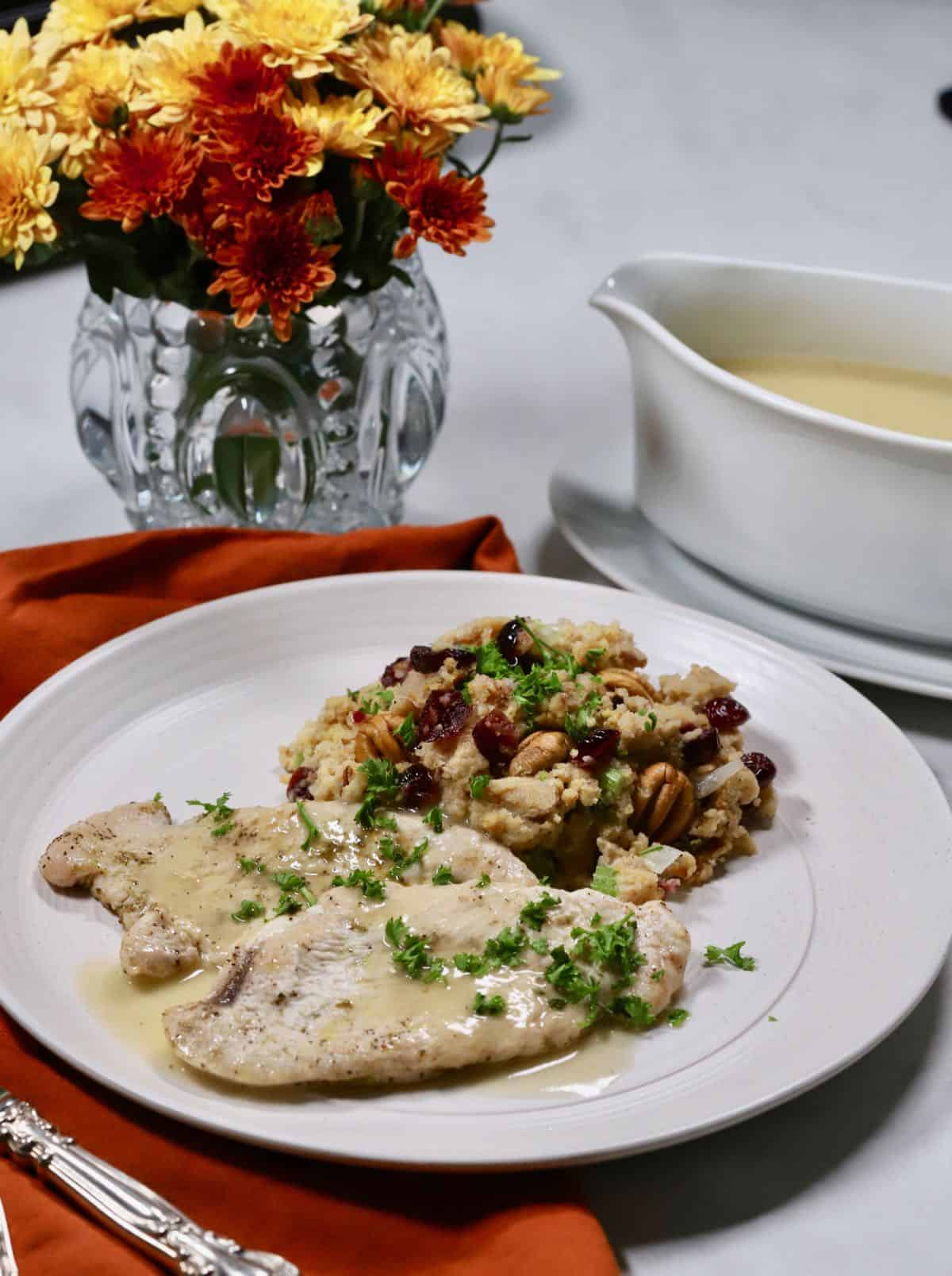 Turkey cutlets, gravy and dressing on a white plate.