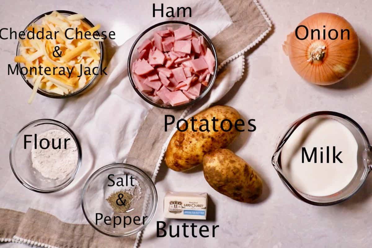 Ham, potatoes, milk, and flour on a cutting board.
