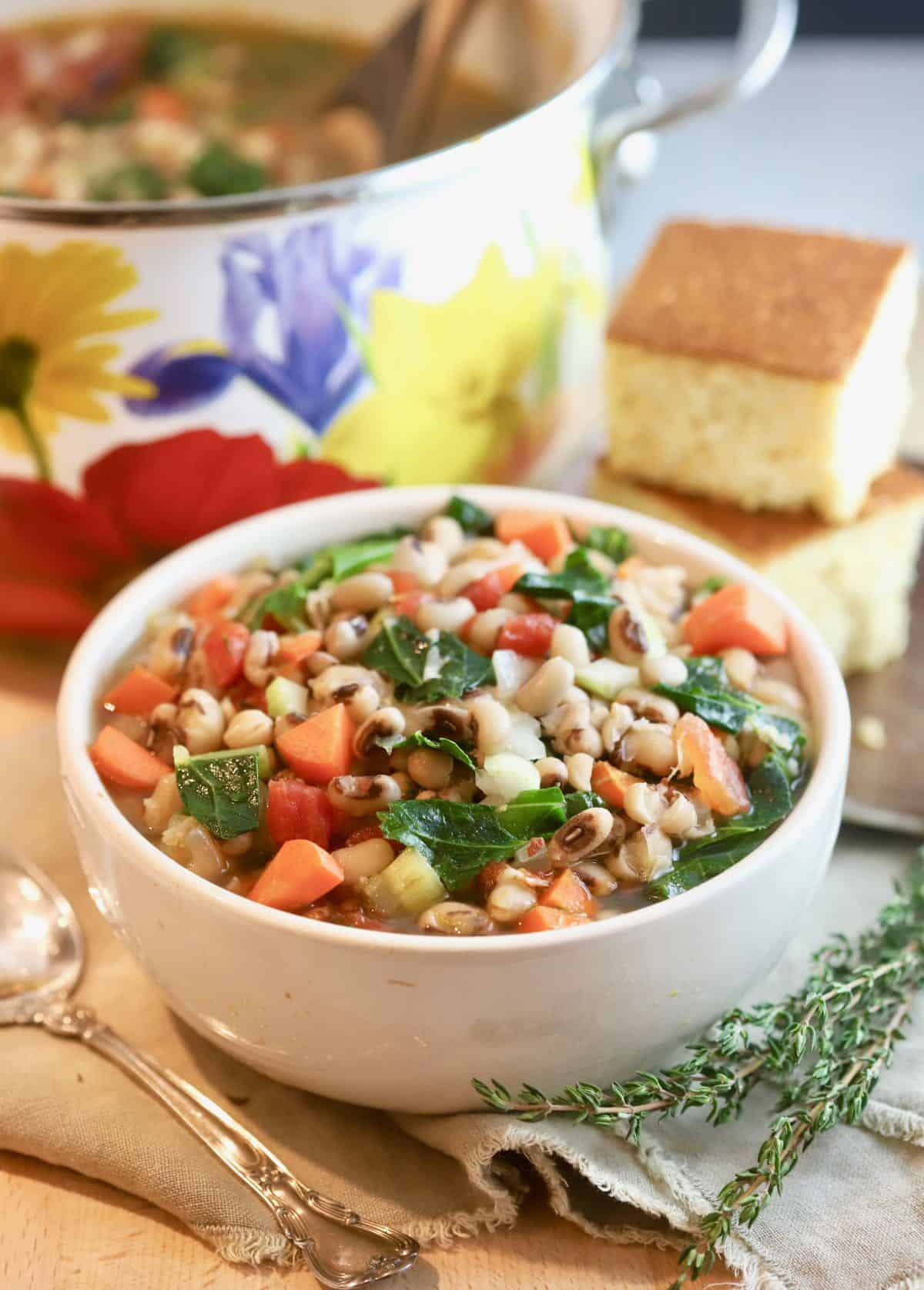 A bowl of black-eyed pea soup with cornbread.