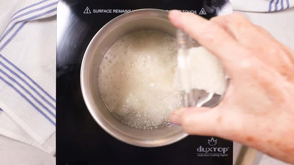 Adding grits to boiling water in a saucepan.