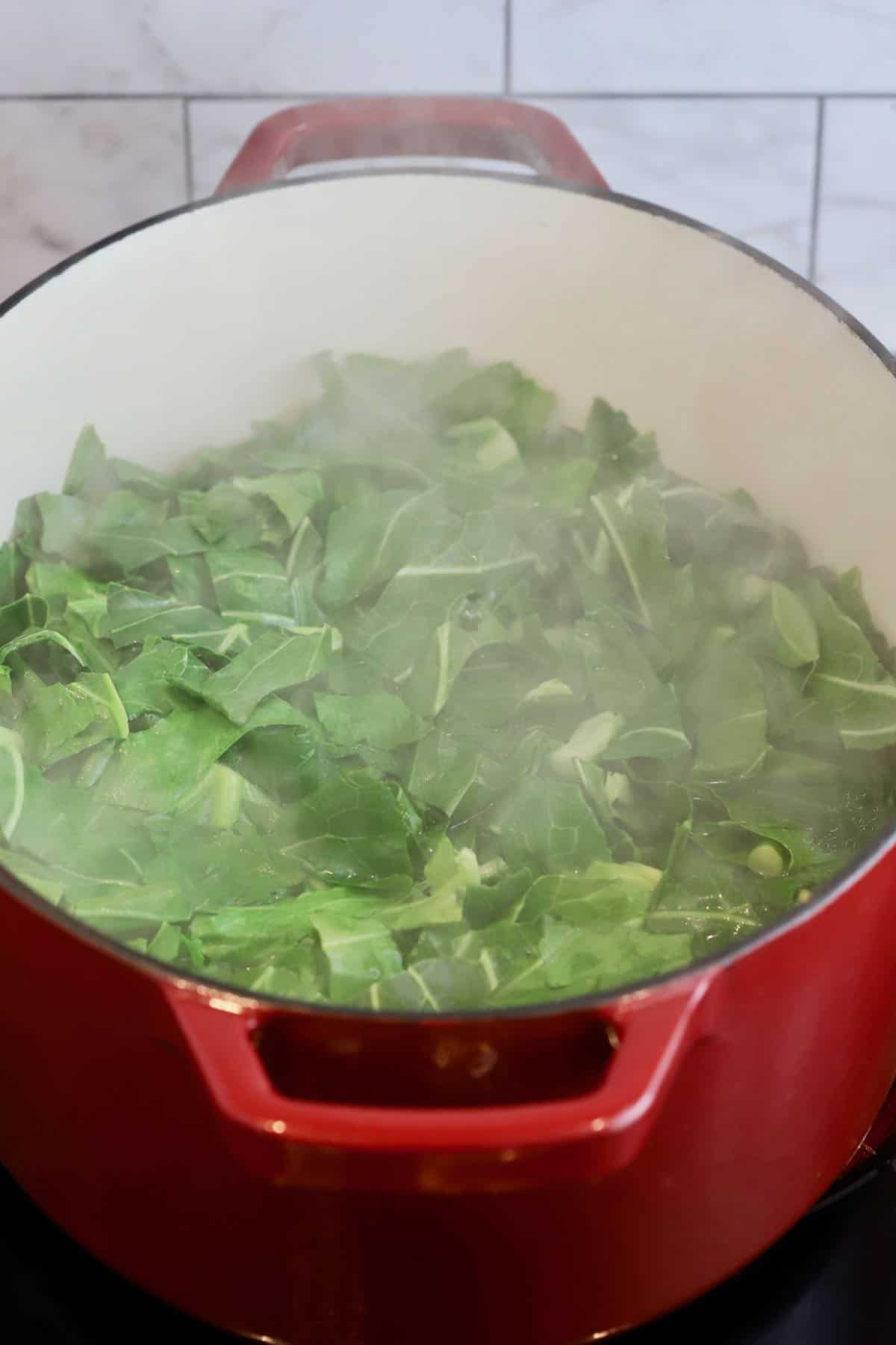 Collard greens cooking in a large Dutch oven.
