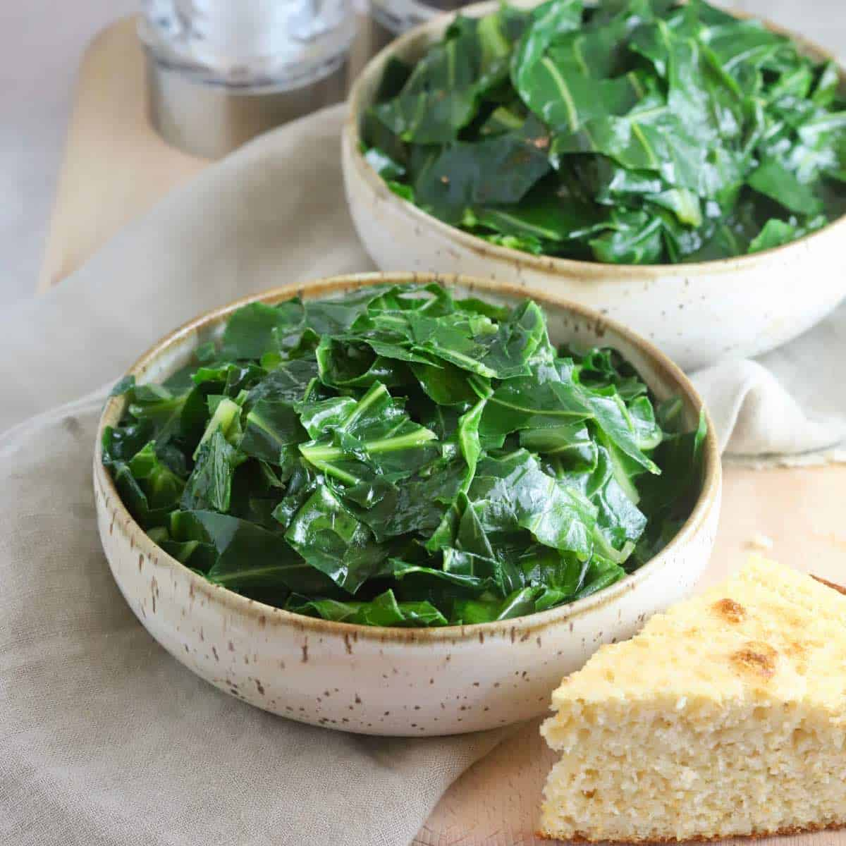 Two bowls of cooked collard greens.