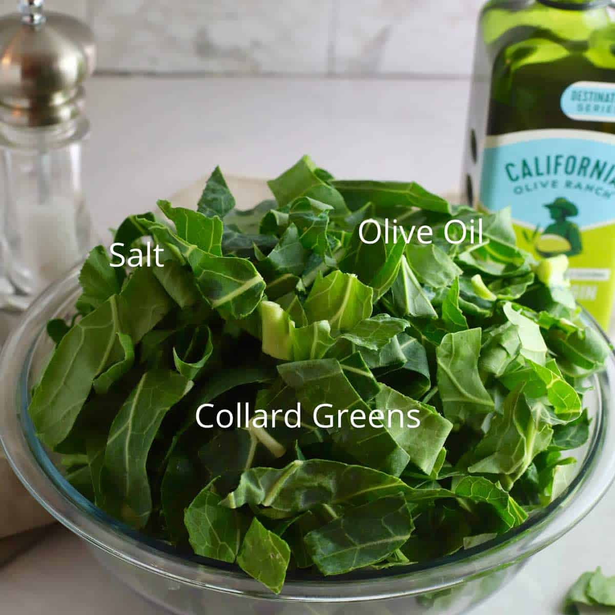 A large bowl of uncooked collard greens, a bottle of olive oil and salt.
