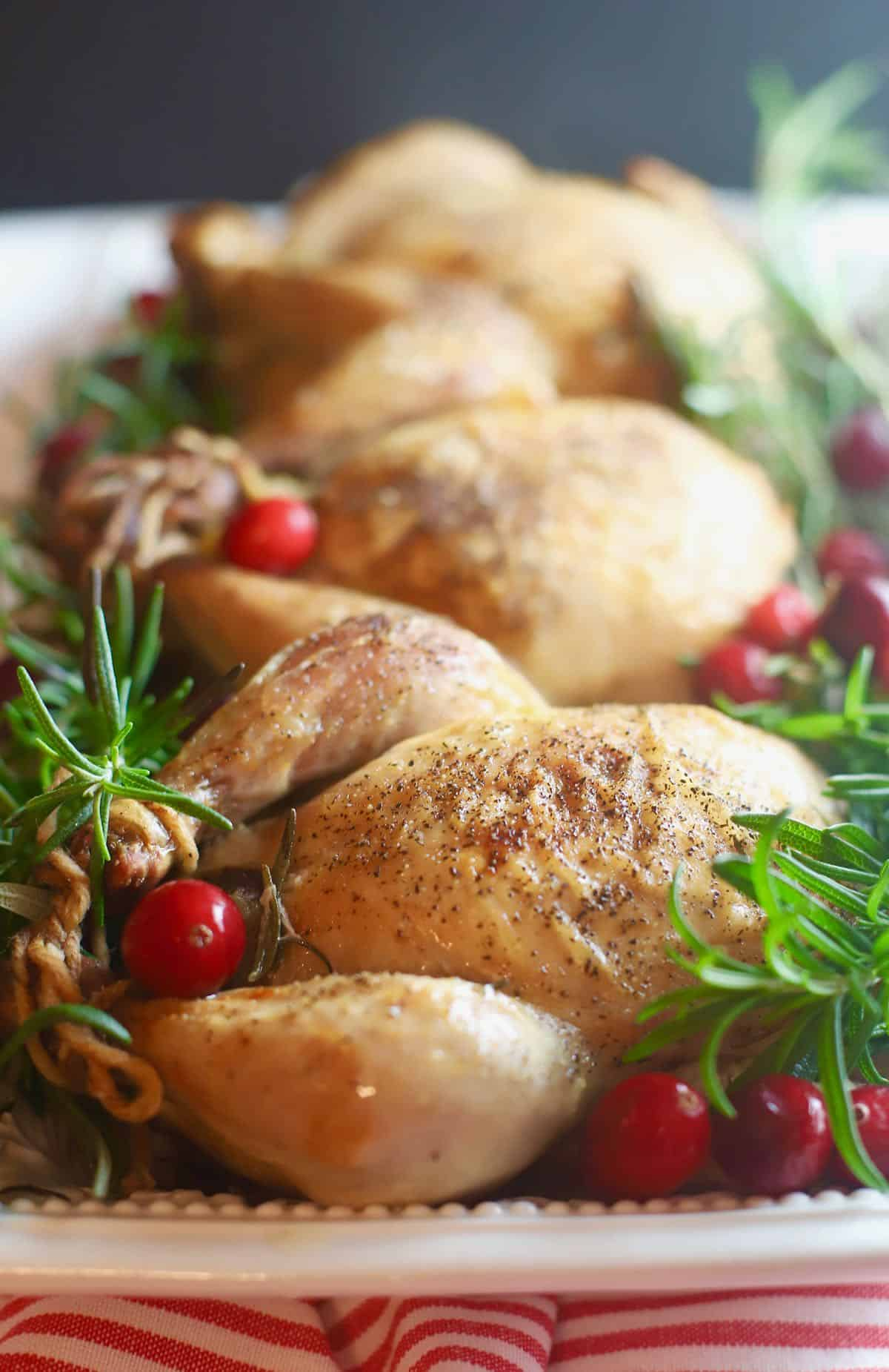 Three oven-roassted Cornish hens on a serving platter.
