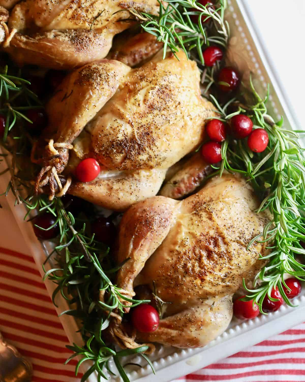 Three Cornish hens on a serving plate garnished with rosemary and cranberries.