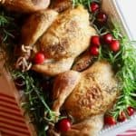 Three Cornish Hens on a serving platter and garnished with rosemary and thyme.