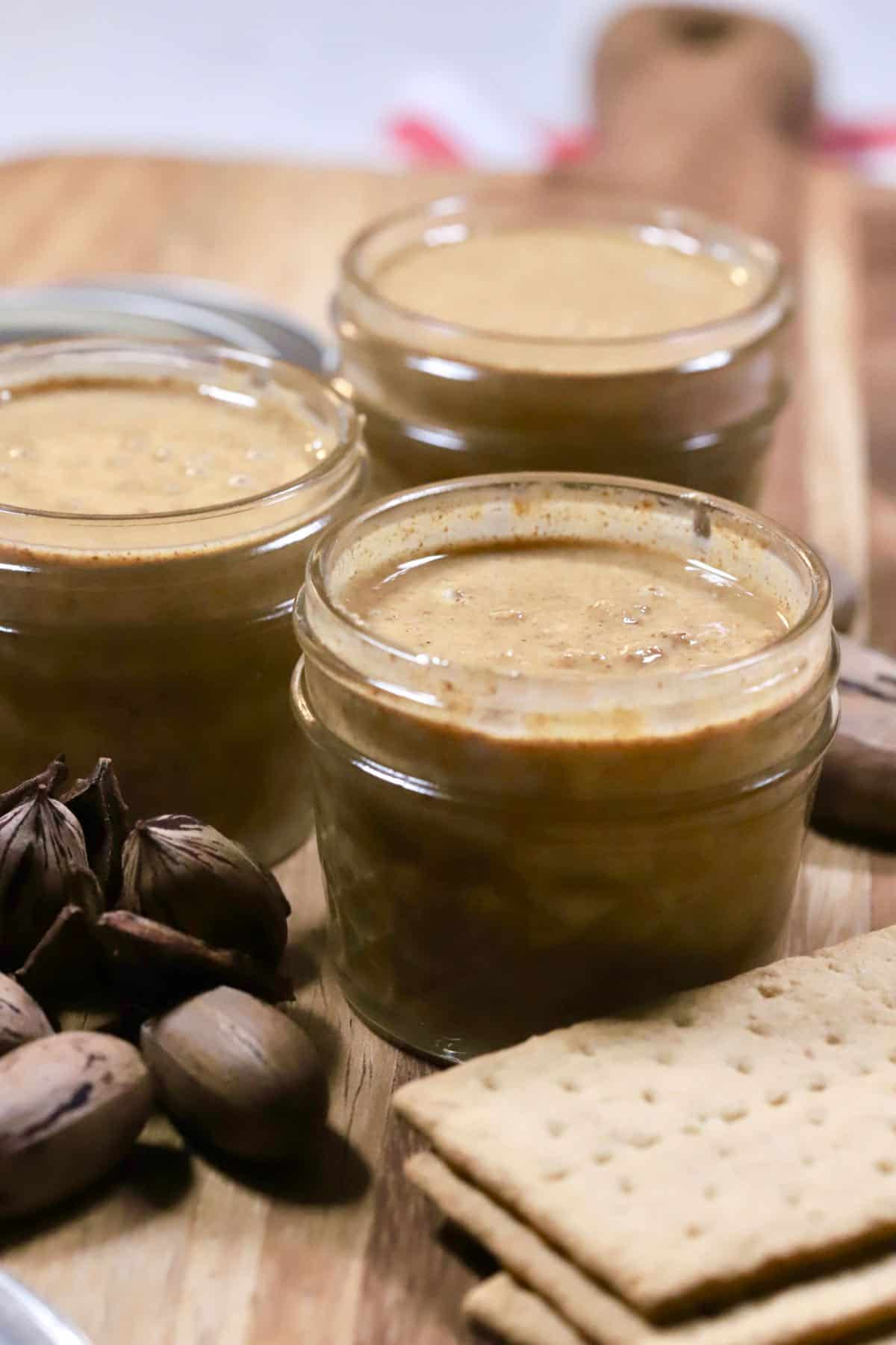 Three jars of pecan butter with graham crackers.