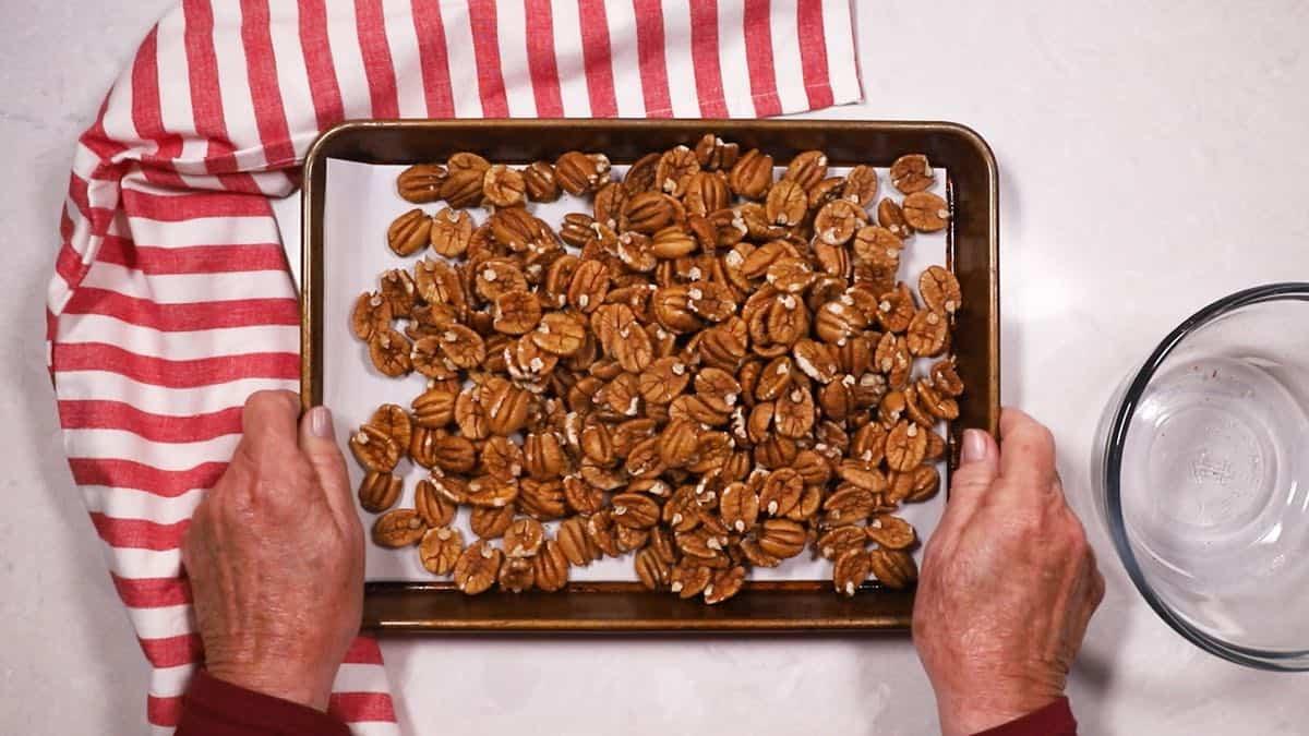 Pecan halves on a baking sheet.