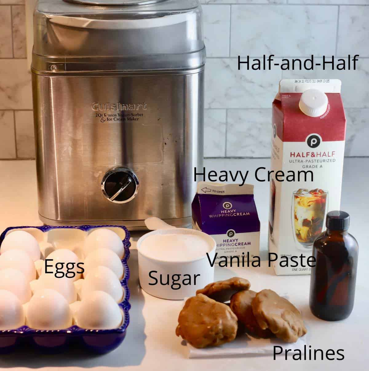 An ice cream maker and ingredients on a kitchen counter.