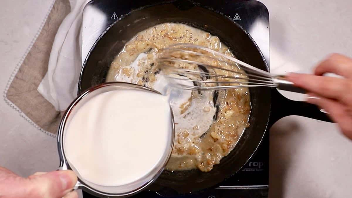 Making a sauce in a skillet by adding cream to cooked flour.