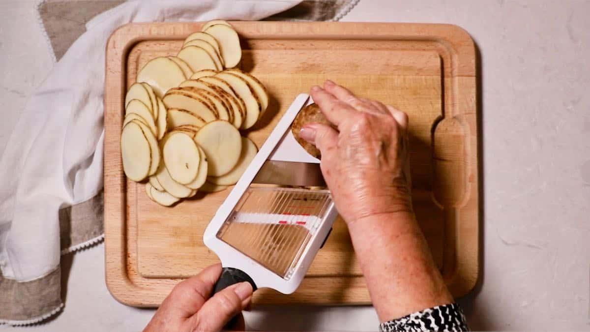 Slicing potatoes with a mandolin.