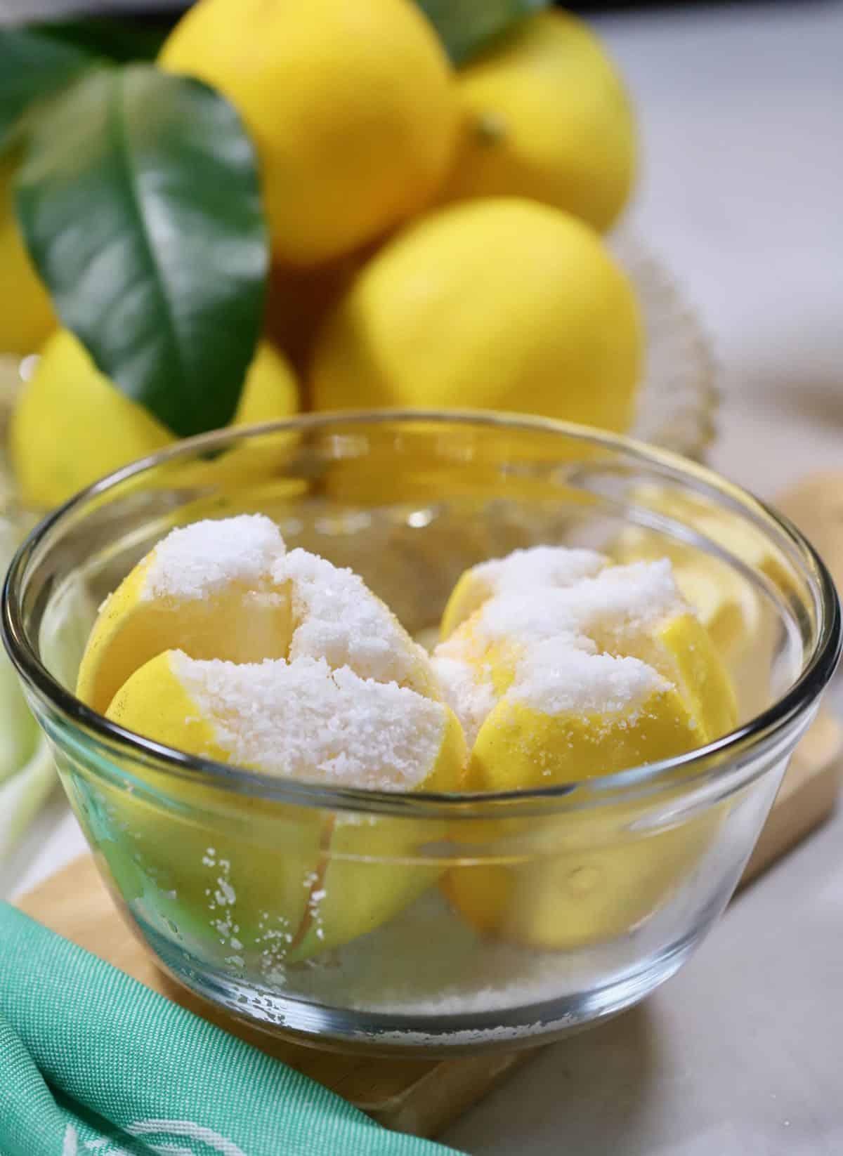 A bowl of lemons with salt on them.