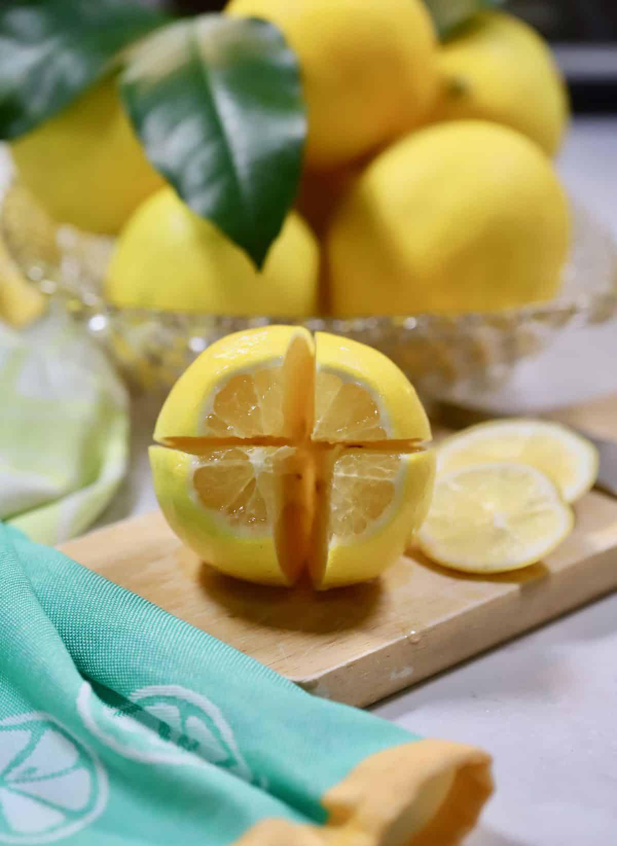 A lemon cut into quarters on a cutting board.