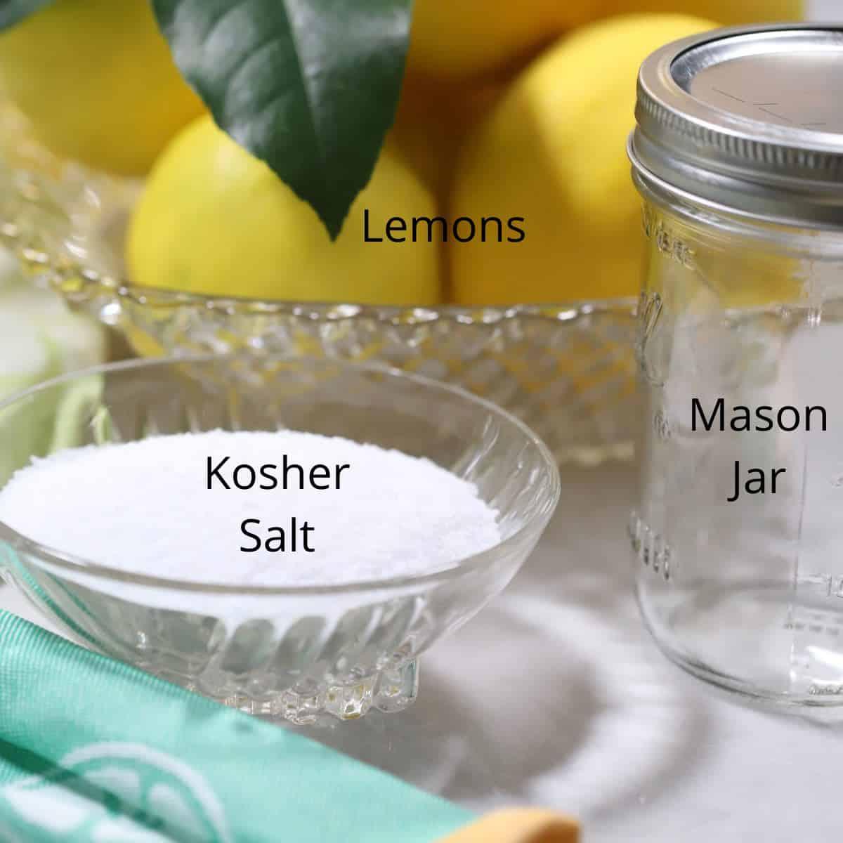 A bowl of kosher salt, lemons and a mason jar.